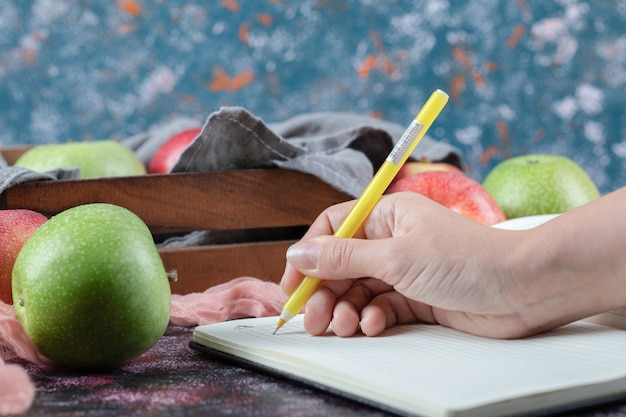 Rote und grüne äpfel auf dem tisch mit einem leeren rezeptbuch beiseite.