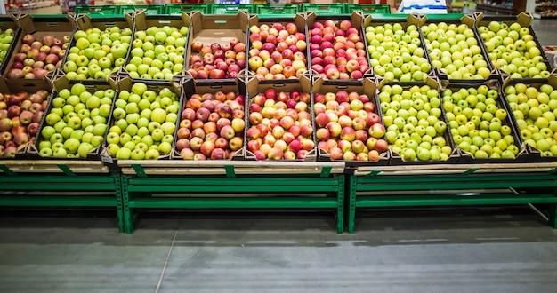 Rote und grüne äpfel auf der markttheke. äpfel in den kartons im lebensmittelregal.