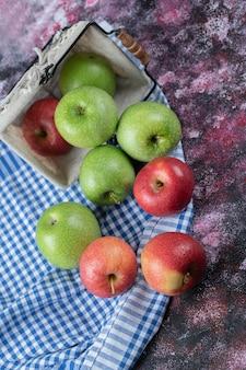 Rote und grüne äpfel aus einem korb auf kariertem tuch heraus.