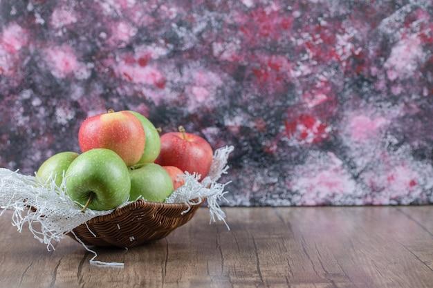 Rote und grüne äpfel in einem holzkorb auf dem tisch.