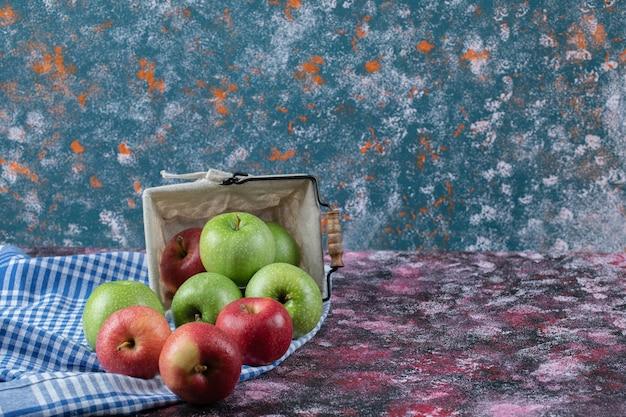 Rote und grüne äpfel in einem rustikalen korb
