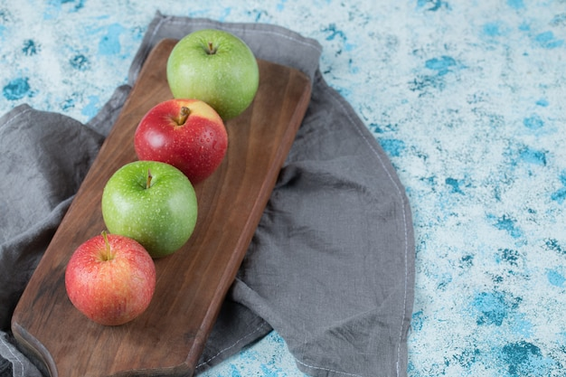 Rote und grüne äpfel in folge auf einem holzbrett.