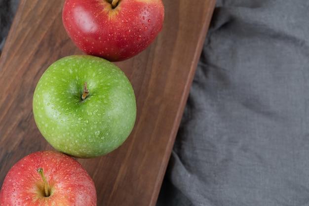 Rote und grüne äpfel in reihe auf holzbrett.