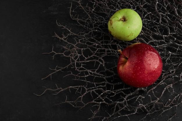 Rote und grüne äpfel isoliert auf einem trockenen ast.