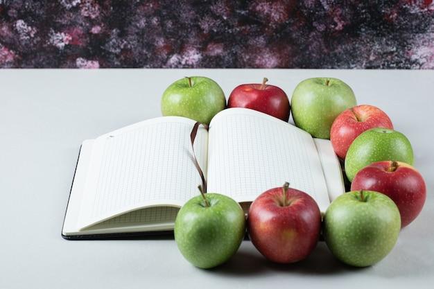 Rote und grüne äpfel mit einem leeren rezeptbuch herum