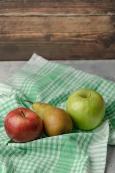 Rote und grüne äpfel mit frischer birne auf grüner tischdecke.