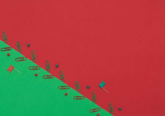 Rote und grüne clips und stifte auf doppeltem grünem und rotem hintergrund. schul- und büromaterial