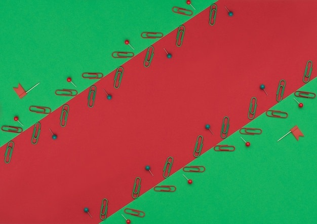 Rote und grüne clips und stifte auf doppeltem grünem und rotem hintergrund