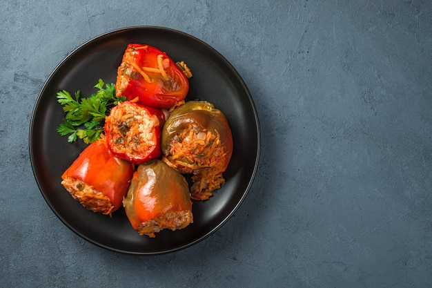Rote und grüne gefüllte paprika auf dunklem hintergrund. paprika mit pute, reis und gemüse.
