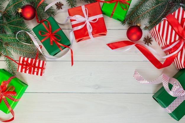 Rote und grüne geschenke mit bändern und schleifen, zweige der grünen fichte mit weihnachtsdekorationen auf einem weißen hölzernen hintergrund