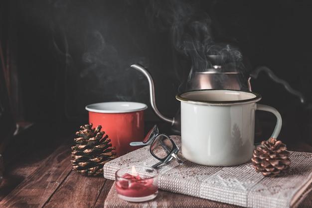 Rote und grüne kaffeetasse, rosenkerze, notizbuch, wasserkocher und tannenzapfen auf holztisch mit dunkler wand, retro-effekt