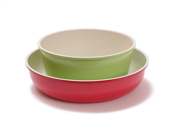 Rote und grüne keramische kochküchenpfannen auf weißem lokalisiertem hintergrund.