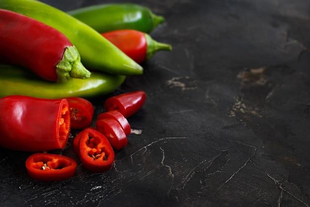 Rote und grüne paprika auf dunklem hintergrund
