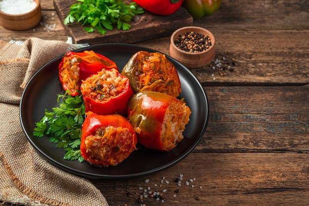 Rote und grüne paprika gefüllt mit fleischreis und gemüse in einem schwarzen teller auf holzuntergrund