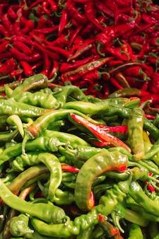 Rote und grüne paprikas auf einem lokalen marktzähler