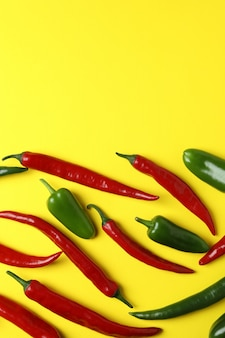 Rote und grüne peperoni auf gelbem hintergrund