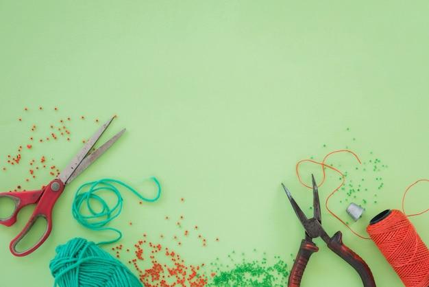 Rote und grüne perlen; schere; zangen und spule auf grünem hintergrund
