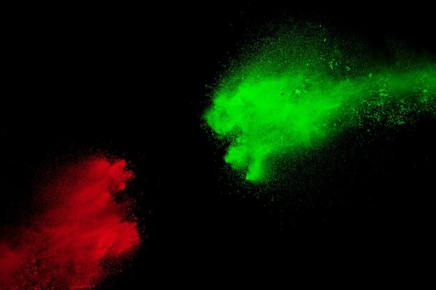 Rote und grüne pulverexplosion auf schwarzem hintergrund.