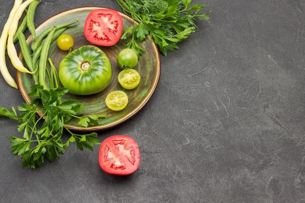 Rote und grüne tomate auf teller. rote tomaten und petersilie auf dem tisch. platz kopieren. schwarzer hintergrund. ansicht von oben