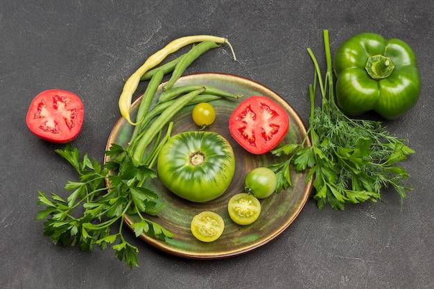 Rote und grüne tomate, grüne bohnen auf grüner platte. pfeffer und petersilie auf dem tisch. schwarzer hintergrund. ansicht von oben