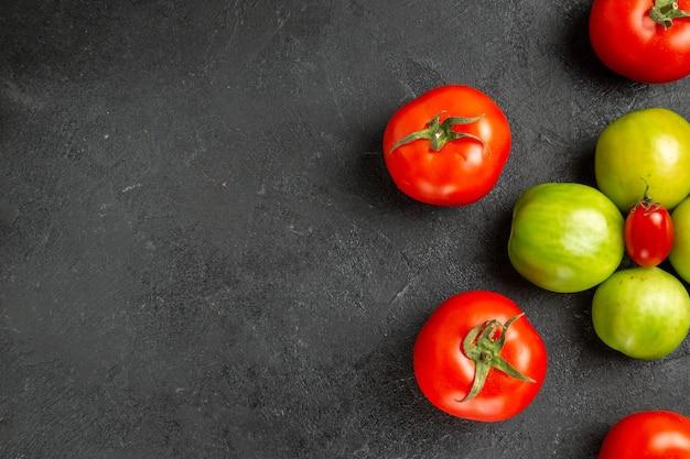 Rote und grüne tomaten der draufsicht um eine kirschtomate rechts von dunklem grund mit kopierraum