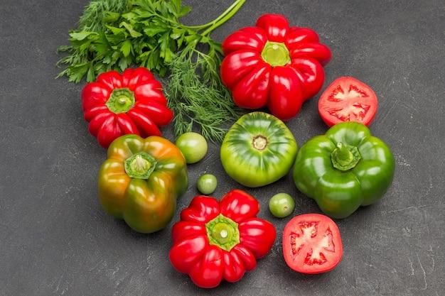 Rote und grüne tomaten und paprika. schwarzer hintergrund. ansicht von oben