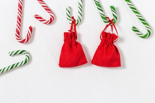 Rote und grüne zuckerstangen mit kleinen geschenken auf weißem hintergrund.