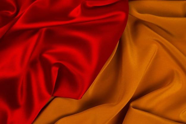 Rote und orangefarbene seiden- oder satin-luxus-stoffbeschaffenheit kann als abstrakter hintergrund verwendet werden. ansicht von oben.