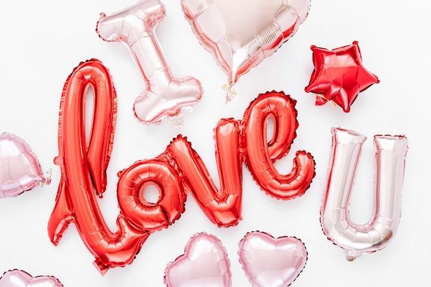 Rote und rosa folienballons in form des wortes