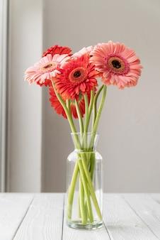 Rote und rosa gerbera-gänseblümchen in vase auf dem tisch, minimalistischer stil. platz kopieren