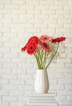 Rote und rosa gerbera-gänseblümchen in weißer vase auf bücherstapel, minimalistischer stil, mock-up-design
