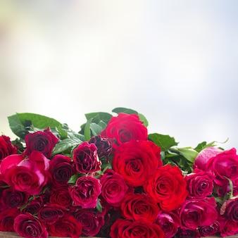 Rote und rosa rosen auf hölzernem rand lokalisiert