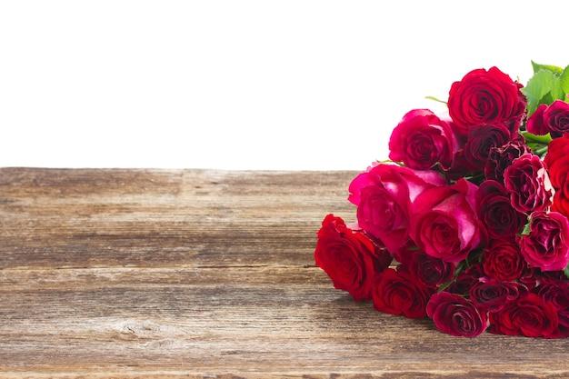 Rote und rosa rosen auf hölzernem tischrand lokalisiert
