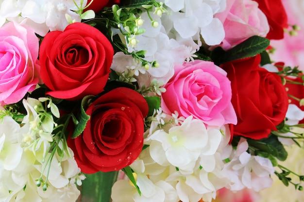 Rote und rosa rosenboutiqueblume verzieren im hochzeitsgewebe