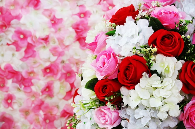 Rote und rosa rosenboutiqueblume verzieren in der hochzeit und verwischen orchidee