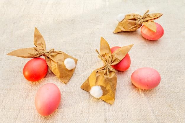 Rote und rosafarbene eier für ostern mit papierhäschen