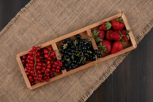 Rote und schwarze johannisbeeren der draufsicht mit erdbeeren auf einem hölzernen hintergrund