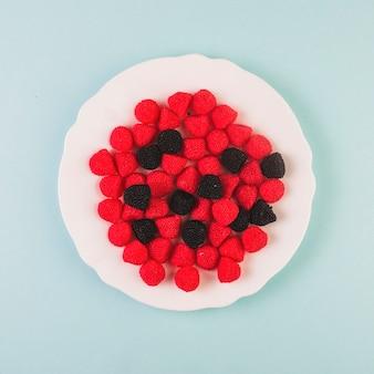 Rote und schwarze moosbeersüßigkeiten auf platte