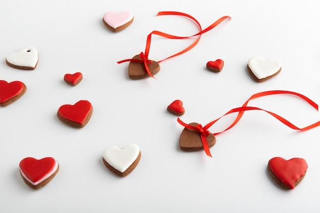 Rote und weiße herzen mit bändern auf weißem hintergrund. muttertag. frauentag. valentinstag.
