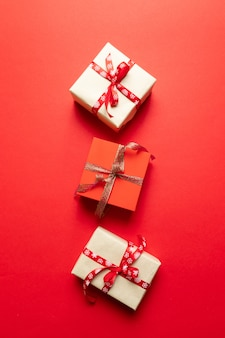 Rote und weiße kraftpapiergeschenkboxen auf rotem hintergrund. minimales konzept des neuen jahres. noel.
