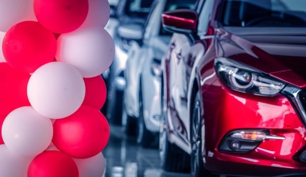 Rote und weiße luftballons, die im modernen autoausstellungsraum auf unscharfem rotem suv-auto der vorderansicht verziert werden. neues und glänzendes luxus-suv-auto im modernen showroom geparkt. autohausbüro. automobilindustrie.