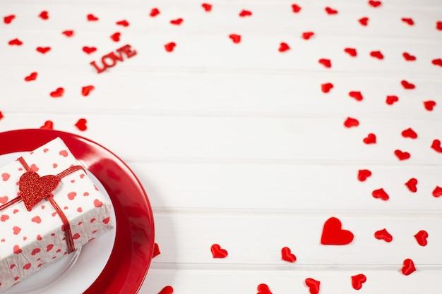 Rote und weiße platte, geschenk in einer schachtel und festliches dekor herzförmig. valentinstag konzept.