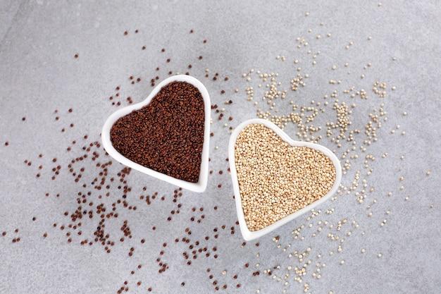 Rote und weiße quinoa in herzförmiger schüssel auf steinhintergrund