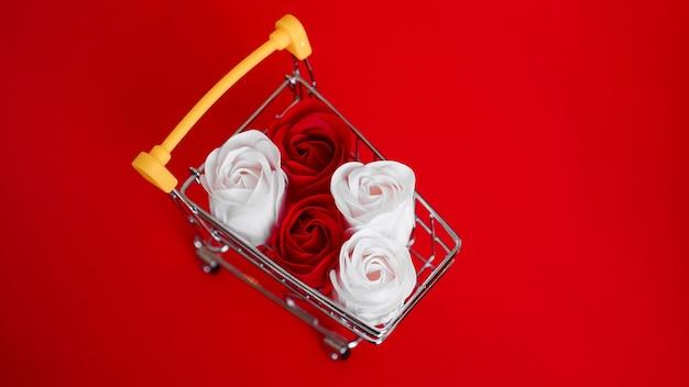 Rote und weiße rosen blühen auf einkaufswagen auf rot