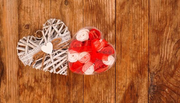 Rote und weiße rosen und weißes herz des valentinstags auf holz. draufsicht