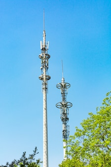 Rote und weiße turm der kommunikation mit einer menge von verschiedenen antennen unter blauem himmel und wolken