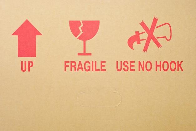 Rote verpackungssymbole auf braunem karton
