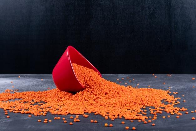 Rote verstreute linsen der seitenansicht in der roten schüssel auf dunklem stein und schwarzem tisch