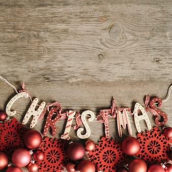 Rote verzierungen mit weihnachtsbuchstaben und platz für text