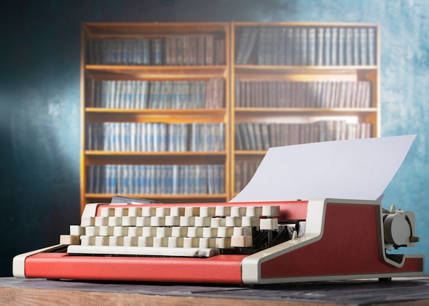 Rote vintage schreibmaschine und bücherregal